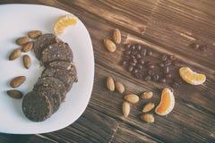 Kawa groszkuje, migdałowe dokrętki, tangerine plasterki i czekoladowy kiełbasiany ciasto na drewnianej powierzchni, Rocznika prze obraz stock