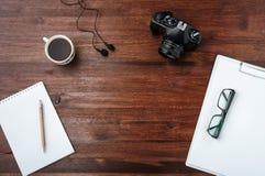 Kawa i kamera na ciemnym drewno stole z papierem, pióro, szkła Odgórny widok Obraz Stock