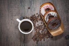 Kawa i pączek na drewnianym stole Fotografia Stock