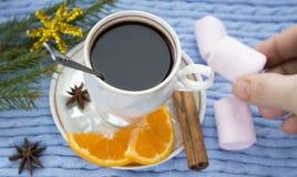 Kawa i ręka z marshmallows na błękitnym dzianiny tle Zdjęcie Stock