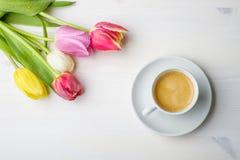Kawa i tulipany na białym drewno stole z niektóre wodą na t Obrazy Stock