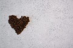 Kawa istotny olej w szklanej butelce, kawowe fasole w kształcie serce na popielatym tle fotografia royalty free
