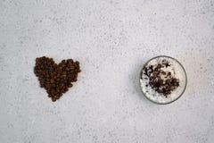 Kawa istotny olej w szklanej butelce, kawowe fasole w kształcie serce na popielatym tle zdjęcia royalty free