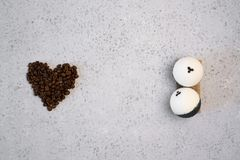 Kawa istotny olej w szklanej butelce, kawowe fasole w kształcie serce na popielatym tle zdjęcie royalty free