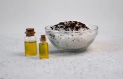 Kawa istotny olej w szklanej butelce, kawowych fasolach i kąpielowej soli na popielatym tle, obraz royalty free