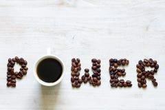 Kawa jest władzy pojęciem z fasolami i szkłem na drewnianym tle obraz royalty free