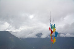 Kawa karpo snow mountains covered by cloud. Shangri-la, China. Tibetan flags colored in front Royalty Free Stock Images