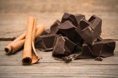 Kawałki czekoladowy bar z cynamonem na drewnianym tle Obraz Royalty Free