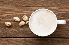 Kawa na drewnianym stole z pistacjowymi dokrętkami Fotografia Stock