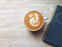 Kawa na drewno stole z książką Fotografia Stock