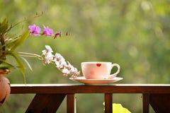 Kawa na poręczu z storczykowym kwiatem na tarasie Obrazy Royalty Free