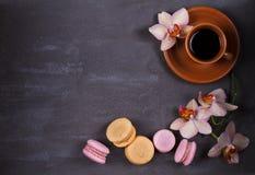 Kawa, orchidee, tortowy macaron i macaroon na szarym tle od above, Obrazy Stock