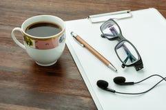 Kawa, pióro, hełmofony i szkła na drewno stole, Obrazy Stock