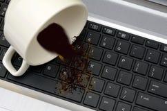 Kawa rozlewająca z filiżanki na laptop klawiatury szkody pojęciu Obraz Stock