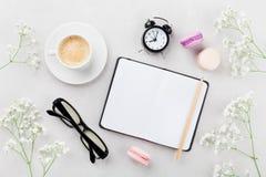 Kawa, tortowy macaron, notatnik, eyeglasses, budzik i kwiat dla śniadania na stołowym odgórnym widoku, Kobiety pracujący biurko M Obraz Royalty Free