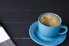 Kawa w błękitnej filiżance z dopasowywania naczyniem na czarnym drewnianym tle obraz royalty free