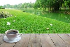 Kawa w Białej filiżance na Drewnianym przedpolu i kwiacie na podłoga z tłem ogródu lub parka zdjęcie stock