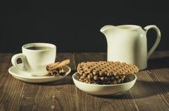 kawa w białej filiżance z kijami cynamon, creamer i ciastka,/kawa w białej filiżance z kijami cynamon, creamer i zdjęcia stock