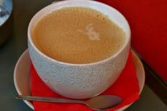 Kawa w białej filiżance z wzorem na spodeczku z czerwoną pieluchą zdjęcie royalty free