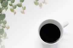 Kawa w Białym kubku z małymi liśćmi na białej ściennej miękkiej plamie dla tła, rocznika kolor zdjęcia royalty free