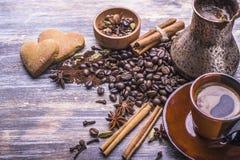 Kawa w filiżance, kawowe fasole, pikantność, ciastka w formie serca na drewnianym tle Zdjęcia Royalty Free