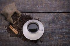 Kawa w filiżance, kawowe fasole, pikantność, ciastka w formie serca na drewnianym tle Obraz Stock