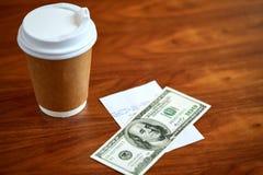 Kawa w papierowej filiżance, rachunku i pieniądze na stole, Zdjęcie Stock