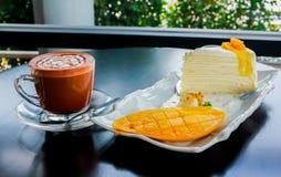 Kawa z kawałkiem mangowy cheesecake na stołowy drewnianym Fotografia Royalty Free