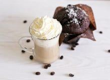Kawa z kremową i czekoladową babeczką na białym drewnianym tle Zdjęcie Royalty Free