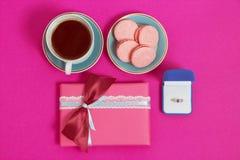 Kawa z macarons i pierścionek na różowym tle Oferta małżeństwo Odgórny widok, stonowany wizerunek Fotografia Royalty Free