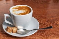 Kawa z wzorem piana jest w spodeczku który jest teaspoon i dwa kawałkami trzcina cukier, zdjęcia royalty free