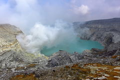 Kawah Ijen volcanic crater emitting sulphuric gas still used for sulphur mining in East Java Stock Photos