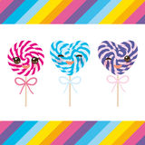 Kawaii Valentine`s Day Heart shaped candy lollipops with bow, colorful spiral candy cane with bright rainbow stripes. on stick wit Stock Images