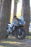 Kawasaki motorcycle in the shade under the pines on a bright Sunny day Stock Photos