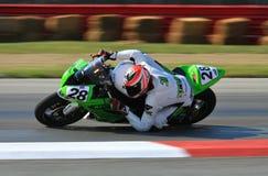 Kawasaki race motorcycle. Pro rider Ryan Kerr drags his knee on the sharp turn on the Kawasaki super bike stock images