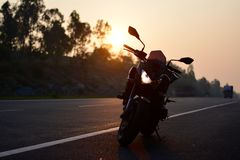 Kawasaki z800 silhouette. Here is a picture of kawasaki z800 silhouette, the sun rises in the background, giving the image an orange glow and an amazing Royalty Free Stock Photo