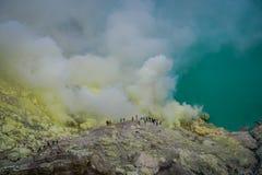 KAWEH IJEN, ИНДОНЕЗИЯ: Туристские hikers с рюкзаками и уходом за лицом маскируют увиденную обозревая шахту серы и вулканический к Стоковая Фотография RF