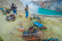 KAWEH IJEN, INDONESIA - 3 MARCH, 2017: Local miners using wheelbarrows to transport sulfur and equipment from mine Royalty Free Stock Photo