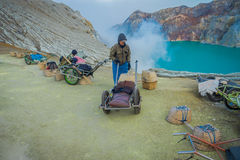 KAWEH IJEN, INDONESIA - 3 MARCH, 2017: Local miners using wheelbarrows to transport sulfur and equipment from mine Stock Image