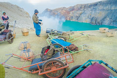 KAWEH IJEN, INDONESIA - 3 MARCH, 2017: Local miners using wheelbarrows to transport sulfur and equipment from mine Royalty Free Stock Image