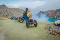 KAWEH IJEN, INDONESIA - 3 MARCH, 2017: Local miners using wheelbarrows to transport sulfur and equipment from mine Royalty Free Stock Photos