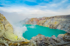 KAWEH IJEN, INDONESIA: Spectacular overview of volcanic crater lake with beautiful blue sky, tourists visible in the. Distance Stock Photography