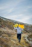 KAWEH IJEN, INDONESIEN: Der lokale Bergmann, der schwere Last des gelben Schwefels trägt, schaukelt herauf Gebirgsseite, touristi lizenzfreie stockfotografie