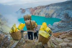 KAWEH IJEN, INDONESIEN: Die lokalen Bergmänner, die schwere Körbe des gelben Schwefels tragen, schaukelt herauf Gebirgsseite, tou lizenzfreie stockbilder
