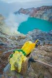 KAWEH IJEN, INDONESIEN: Gelber Schwefel schaukelt innerhalb der Körbe, großartiger vulkanischer Kraterseehintergrund, touristisch lizenzfreies stockfoto