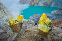 KAWEH IJEN, INDONESIEN: Gelber Schwefel schaukelt innerhalb der Körbe, großartiger vulkanischer Kraterseehintergrund, touristisch stockbild