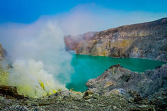 KAWEH IJEN, INDONEZJA: Ładny przegląd siarki kopalnia z górnikami pracuje obok powulkanicznego krateru jeziora, spektakularna nat Zdjęcie Stock
