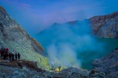 KAWEH IJEN, INDONEZJA: Ładny przegląd siarki kopalnia z górnikami pracuje obok powulkanicznego krateru jeziora, spektakularna nat Obrazy Stock