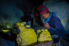 KAWEH IJEN, INDONEZJA - 3 MARZEC, 2017: Obsługuje być ubranym reflektor pracuje w siarki kopalni, ekstrahujące żółte kopalin skał Fotografia Royalty Free