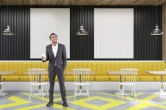 Kawiarnia z plakatami, czernią i kolorem żółtym, mężczyzna Zdjęcie Royalty Free
